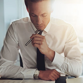 Male Accountant Holding a Pen and Thinking - Lead Image for CPA – Certified Public Accountant Page
