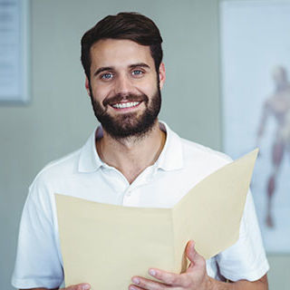 Male Chiropractic Nurse Smiling - Lead Image for Chiropractor Office Page