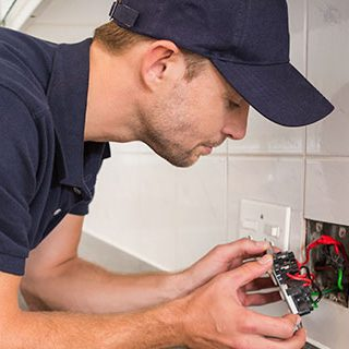 Male Electrician Fixing Wall Socket - Lead Image for Electrician Page