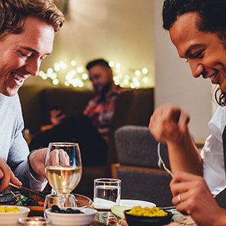 Two Men and Woman Eating at a Restaurant - Lead Image for Family Dining Page