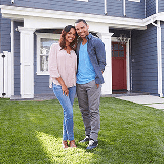 Couple Standing In Front of Their Home and Smiling - Lead Image for Home Page