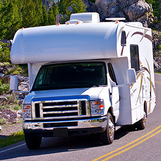 Inszone Insurance RV Insurance Page Banner - Vehicle Cruising Mountain Highway