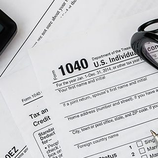 Tax Return Forms with Calculator, Pen and Eye Glasses on Table - Lead Image for Tax Services Page