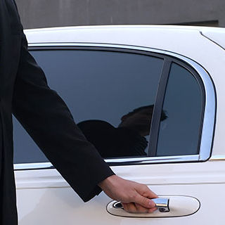 Male Driver in Corporate Attire Holding Car Door Handle - Lead Image for Limo Service Page