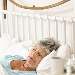 Doctor Staring at Sleeping Elderly Woman - Lead Image for Hospice Page